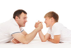 Father and son in arm-wrestling competition. Isolated over white background Royalty Free Stock Images