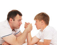Father and son in arm-wrestling competition. Isolated over white background Stock Photo