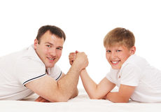 Father and son in arm-wrestling competition. Isolated over white background Royalty Free Stock Image