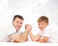 Father and son in an arm-wrestling competition. A happy father and son in and arm-wrestling competition. The image is taken on a light interior background Royalty Free Stock Photos
