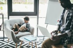 Father and son using gadgets. Father and son in armchair using gadgets in modern interior Stock Photography