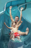 Father And Son With Arms Outstretched On Water Slide Stock Image