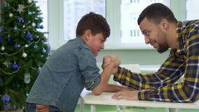 Father and son armwrestle on the table stock video