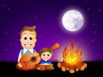 Father and son arount the bonfire Stock Photo