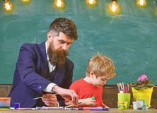 Father and son at the art class. Daddy holding brushes for his boy. Developing creativity.  stock photography
