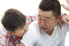 Father and Son. Asian son biting father shoulder while playing on isolated white backrgound Stock Photo