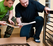Father and son assemble cot. Father and teenage son assemble new baby bed (cot, crib Royalty Free Stock Photography