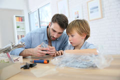 Father and son assembling an aeroplane toy. Father and son assembling airplane mock-up Royalty Free Stock Photography