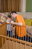 Father and son assembling cot for a newborn at. Portrait of father and son assembling together cot for a newborn at home. Family leisure concept royalty free stock image