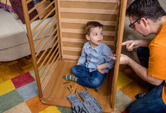 Father and son assembling cot for a newborn at. Portrait of father and son assembling together cot for a newborn at home. Family leisure concept royalty free stock photography