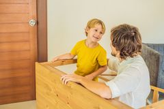 Father and son assembling furniture. Boy helping his dad at home. Happy Family concept royalty free stock photos