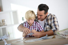 Father and son assembling a plane toy. Father and kid making a plane model Royalty Free Stock Photo