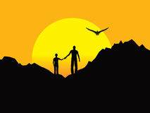 Father and Son atop Rocky Formation at Sunset. Royalty Free Stock Photos