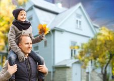 Father and son with autumn maple leaves over house royalty free stock images