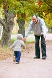 Father and son in autumn park Stock Photos