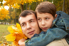 Father and son in autumn park. Son with a bouquet of autumn leaves hugging his father royalty free stock images