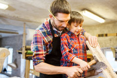 Father and son with ax and wood plank at workshop Stock Image