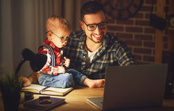Father and son baby work at home at computer in dark Royalty Free Stock Images