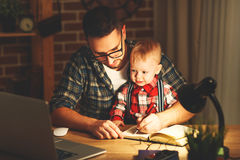 Father and son baby work at home at computer in dark Stock Photography