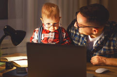Father and son baby work at home at computer in dark Royalty Free Stock Photo