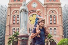 Father and son in the background Notre dame de Saigon Cathedral, build in 1883 in Ho Chi Minh city, Vietnam.  stock photo