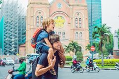 Father and son in the background Notre dame de Saigon Cathedral, build in 1883 in Ho Chi Minh city, Vietnam.  royalty free stock photo