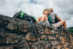 Father and son backpacker traveler rest together on old stone wa Stock Images