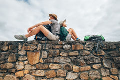 Father and son backpacker traveler rest together on old stone wa. Ll Stock Photography