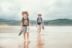 Father and son backpacker traveler walk on sand ocean beach Stock Photo