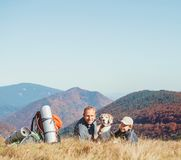 Father and son backpackers hikers rest on mountain hill with their beagle dog royalty free stock photo