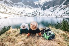 Father and son backpackers rest near the mountain lake and enjoy. Snowy peaks. Spring-summer hiking Royalty Free Stock Images