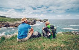 Father and son backpackers rest on the rocky sea side stock images