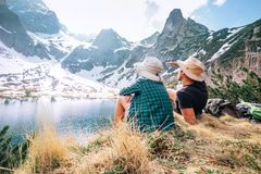 Father and son backpackers sit near the mountain lake and enjoy. Mountain snowy peaks Stock Photography