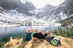 Father and son backpackers sit near the mountain lake and enjoy. Mountain snowy peaks. Spring-summer hiking Stock Image