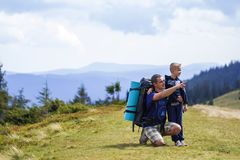 Father and son with backpacks hiking together in scenic summer green mountains. Dad and child standing enjoying landscape mountain. View. Active lifestyle stock photography