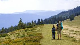Father and son with backpacks hiking together in scenic summer green mountains. Dad and child standing enjoying landscape mountain. View. Active lifestyle stock photos