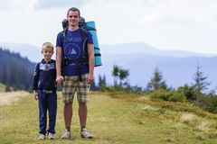 Father and son with backpacks hiking together in scenic summer green mountains. Dad and child standing enjoying landscape mountain. View. Active lifestyle royalty free stock images