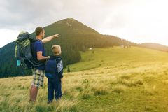 Father and son with backpacks hiking together in summer mountains. Back view of dad and child holding hands on landscape mountain royalty free stock photo