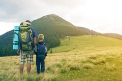 Father and son with backpacks hiking together in summer mountains. Back view of dad and child holding hands on landscape mountain royalty free stock photography