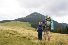 Father and son with backpacks hiking together in summer mountains. Back view of dad and child holding hands on landscape mountain stock images