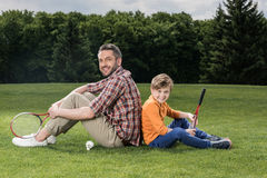 Father and son with badminton racquets sitting on grass and smiling at camera Royalty Free Stock Photos
