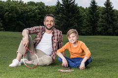 Father and son with badminton racquets sitting on grass and smiling at camera Royalty Free Stock Images