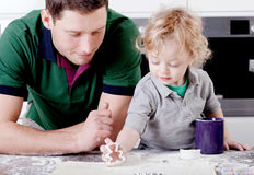 Father and son bake muffins in the kitchen Stock Photography