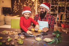 Father and son baking gingerbread Christmas cookies. stock image