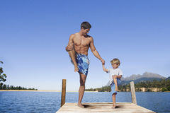 Father and son balancing in lake dock Royalty Free Stock Photos