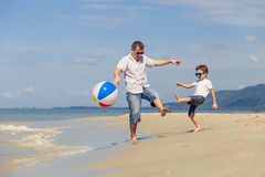Father and son with ball playing soccer on the beach at the day Royalty Free Stock Image