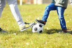 Father and son with ball on soccer pitch, Stock Photo