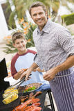 Father And Son Barbequing Stock Photos