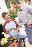Father And Son Barbequing Royalty Free Stock Photo