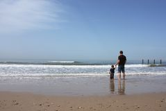 Father and son on the beach. They stand in the water and watch the sea royalty free stock photos